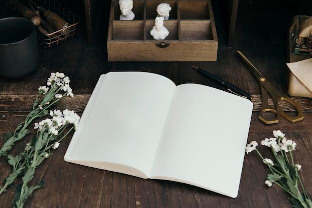 アーティストの机の上の空白のノートブックのモックアップ
