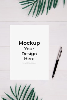 Blank paper mockup and leaf on wooden table