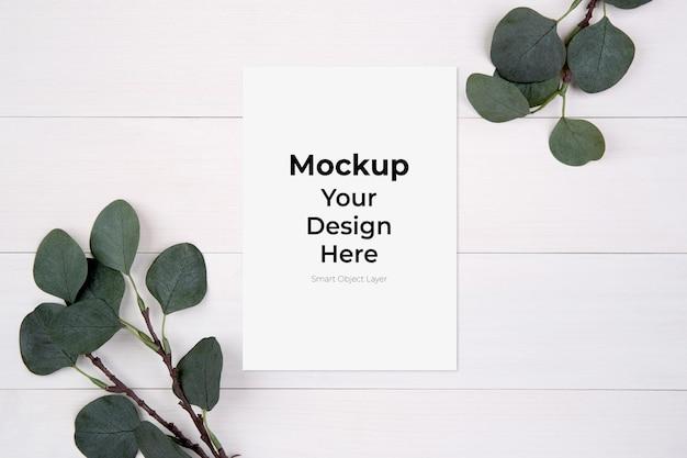 木製のテーブルにモックアップと葉と空白の紙シートコピースペース