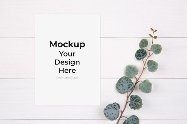 空白の紙のシートのモックアップと木製のテーブルの葉