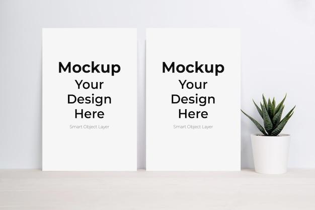 空白の紙のシートのモックアップと木製のテーブルの植物 Premium Psd