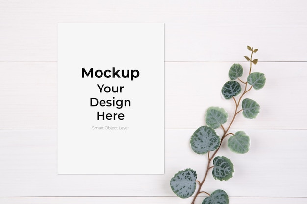 Blank paper sheet mockup and leaf on wooden table