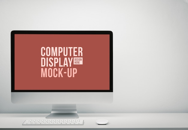 Blank screen computer display for mockup in office interior, work desk with keyboard, mouse. copy space on wall for text.