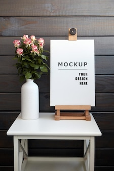Blank stretched canvas mockup on easel on white table with roses in vase