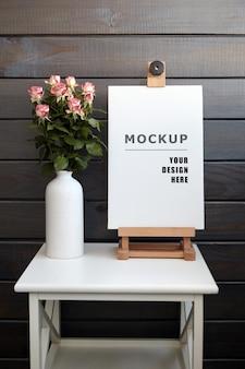 花瓶のバラと白いテーブルのイーゼルに空白のストレッチキャンバスモックアップ