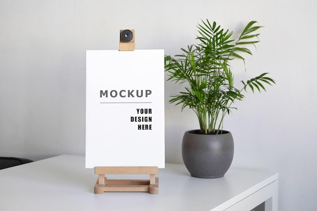 Blank stretched canvas mockup on wooden easel and green houseplant on white table