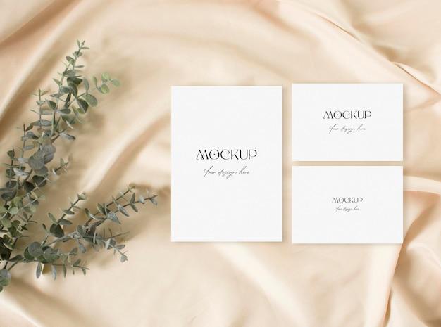 空白の結婚式の招待状は、乾いた草と裸の生地の像でモックアップ