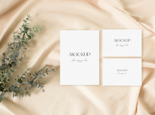 Blank wedding invitation mock up with dry grass and statue on the pnude fabric