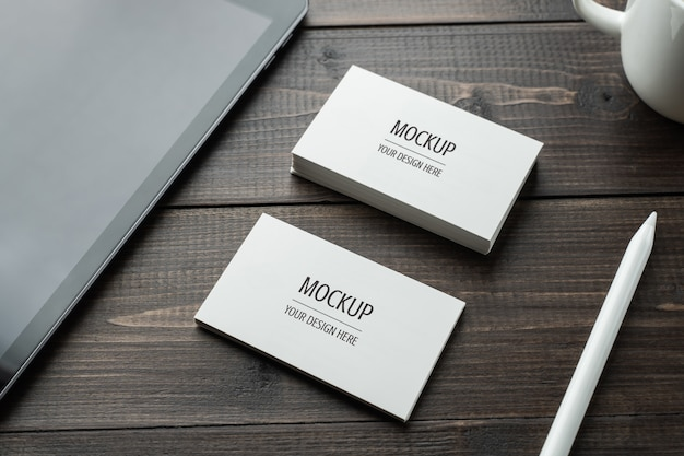 Blank white business card mockup psd and tablet with stylus pencil on wood table