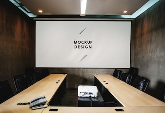 Blank white projector screen mockup in a meeting room