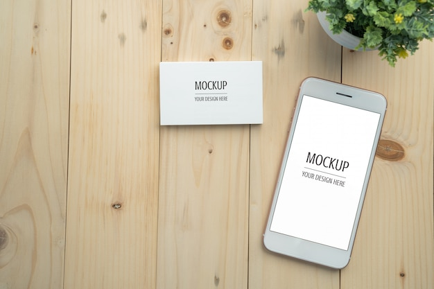 Blank white screen smartphone and business card mockup on wood table and copy space background