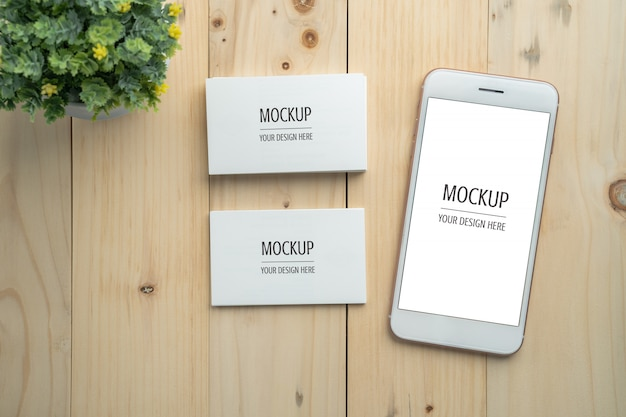 Blank white screen smartphone and business card mockup on wood table