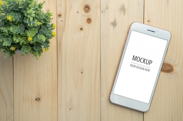 Blank white screen smartphone mockup on wood table and copy space background