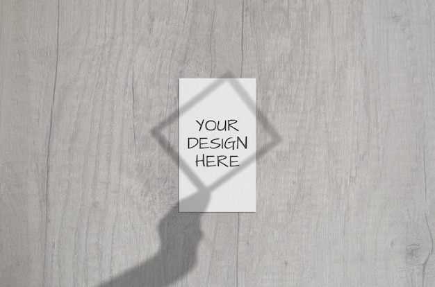 Blank white vertical business card with frame in hand shadow overlay. modern and stylish brand card mock up