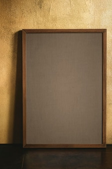 Blank wooden frame  by a grunge yellow wall