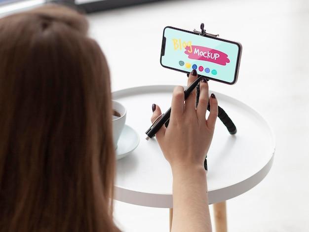Blogger che pubblica su uno smartphone mock-up