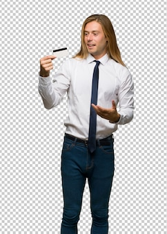 Blond businessman with long hair holding a credit card and surprised