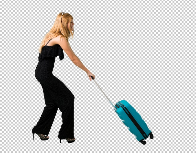 Blond girl traveling and pushing a suitcase that weighs a lot