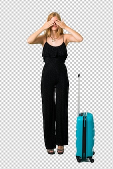 Blond girl traveling with her suitcase covering eyes by hands