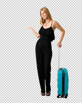 Blond girl traveling with her suitcase pointing back with the index finger presenting a product