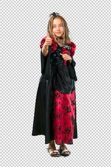 할로윈 휴가를위한 뱀파이어처럼 옷을 입고 금발 아이는 제스처를 엄지 손가락을 포기하고 미소