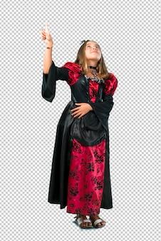 검지 손가락으로 좋은 아이디어를 가리키는 할로윈 휴가를위한 뱀파이어처럼 옷을 입고 금발 아이