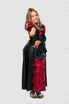 할로윈 휴가를위한 뱀파이어로 옷을 입은 금발의 아이가 손가락을 가리 킵니다.