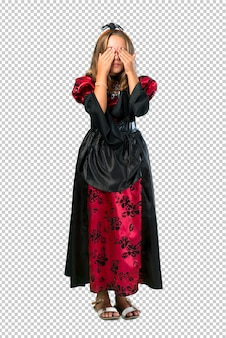 Blonde child dressed as a vampire for halloween holidays covering eyes by hands