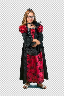 Blonde child dressed as a vampire for halloween holidays keeping arms crossed