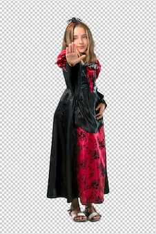Blonde child dressed as a vampire for halloween holidays making stop gesture with her hand