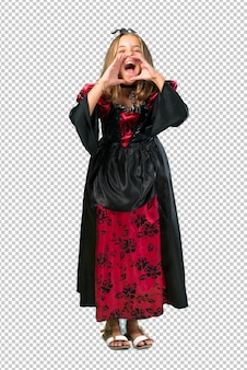 Blonde child dressed as a vampire for halloween holidays shouting with mouth wide open