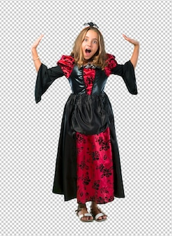 Blonde child dressed as a vampire for halloween holidays with surprise and shocked facial expression