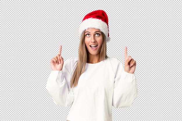 좋은 생각을 검지 손가락으로 가리키는 크리스마스 모자와 금발 소녀