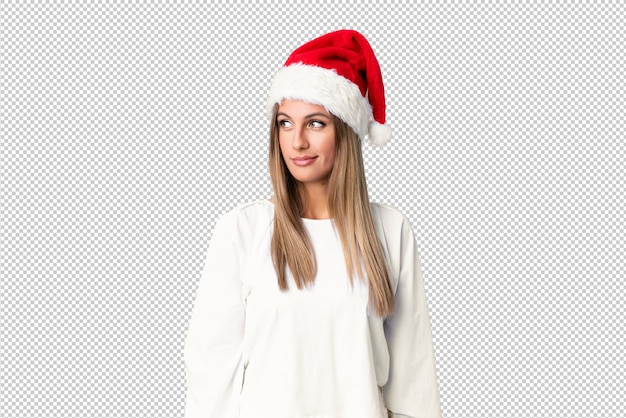 Blonde girl with christmas hat standing and looking to the side