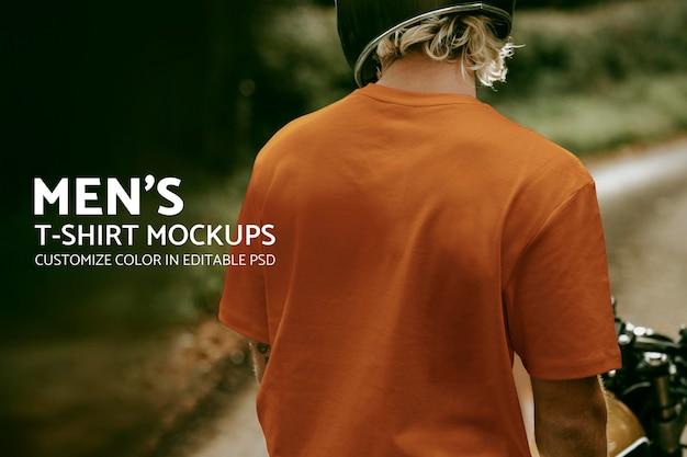 デザインスペースと自転車に座っているオレンジ色のtシャツのブロンドの男