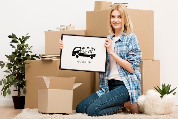 Blonde woman holding moving service frame
