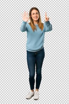 指で6を数える青いシャツと金髪の女性