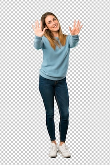 Blonde woman with blue shirt counting ten with fingers
