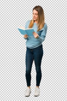 Белокурая женщина с голубой рубашкой держит книгу и наслаждается чтением