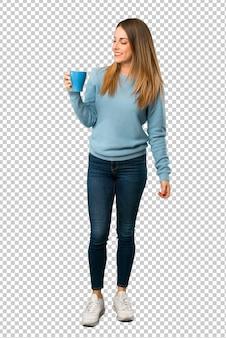 熱い一杯のコーヒーを保持している青いシャツと金髪の女性