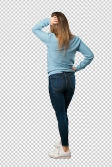 Блондинка с синей рубашкой на спине, оглядываясь назад, почесывая голову