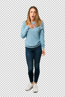Blonde woman with blue shirt surprised and shocked while looking right