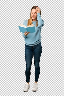 Blonde woman with blue shirt surprised while enjoying reading a book