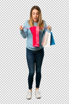 Blonde woman with blue shirt surprised while holding a lot of shopping bags