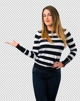 Белокурая девушка-подросток держит воображаемое copyspace на ладони