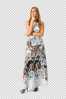 Блондинка молодая девушка в летнем платье много улыбается, положив руки на грудь