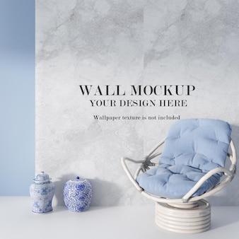 Кресло из ротанга синего цвета перед стеной макета