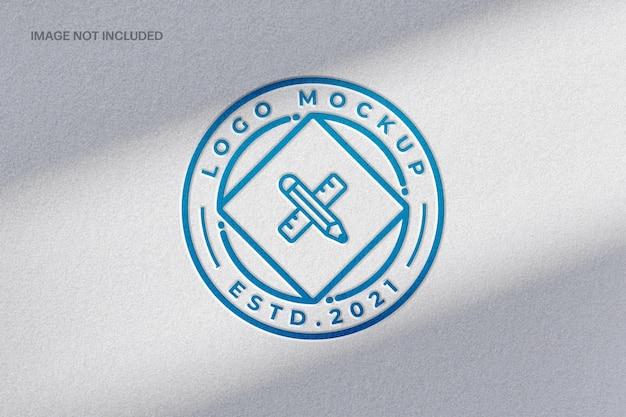 Макет логотипа на синей бумаге с тиснением и наложением теней