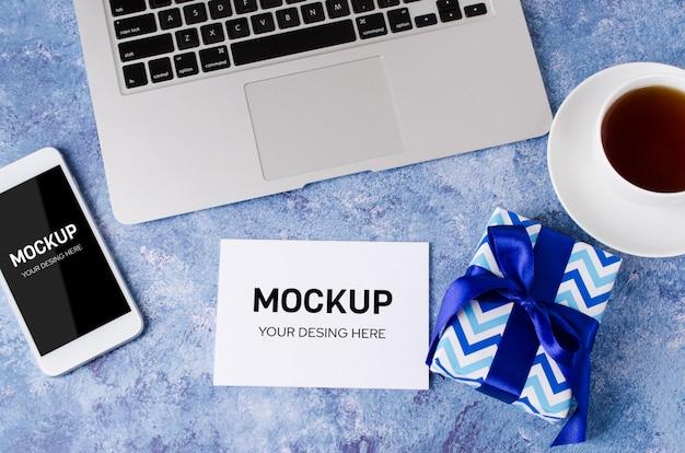 Синяя подарочная коробка, смартфон с черным пустым экраном на офисном столе, ноутбук и чашка чая
