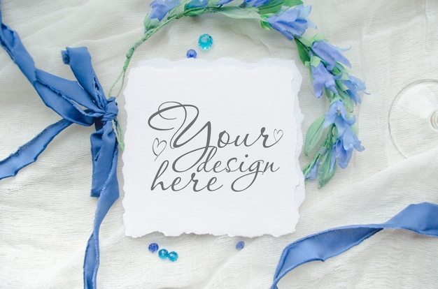 Blue wedding invitation mockup decorated with silk ribbon, crystals and bride wreath